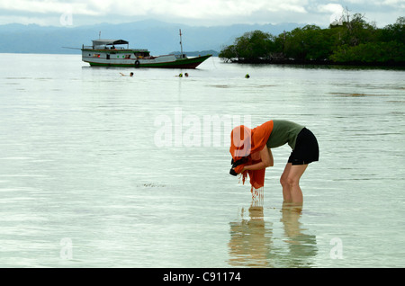 Tourist woman photographing sea life, Raja Ampat islands near West Papua, Indonesia in the coral triangle, Pacific - Stock Photo