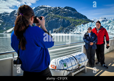 A boat crew member on a tour boat taking pictures of a couple in front of Margerie Glacier, Glacier Bay National - Stock Photo