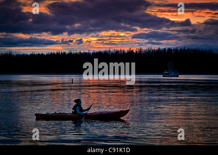Silhouette of a woman sea kayaking in Bartlett Cove at sunset, Gustavus, Glacier Bay National Park & Preserve, Southeast - Stock Photo