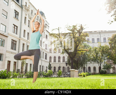 Woman practicing yoga in urban park - Stock Photo