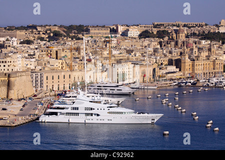 A luxury charter motor yacht complete with helicopter on deck moored in Dockyard Creek next to the district of Birgu - Stock Photo