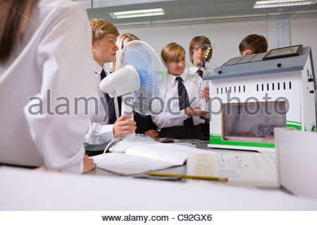 Students experimenting with model wind turbine in science class - Stock Photo