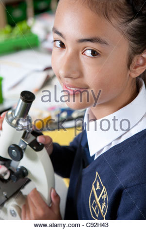 Portrait of smiling female student in school uniform at microscope in science class - Stock Photo