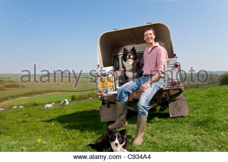 Portrait of shepherd with dog sitting on tailgate of truck - Stock Photo