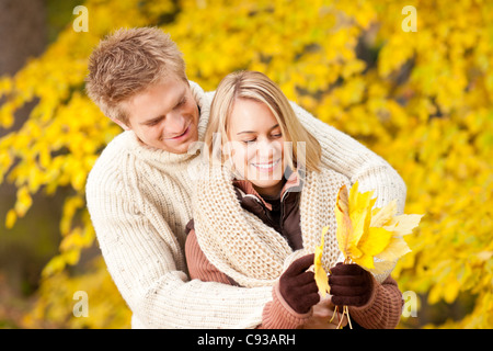 Young playful couple happy picking leaves in autumn park outfit - Stock Photo