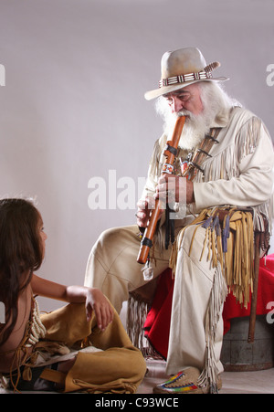 A Native American Indian mountain man playing a flute to a boy - Stock Photo