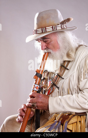 A Native American Indian mountain man playing a flute - Stock Photo