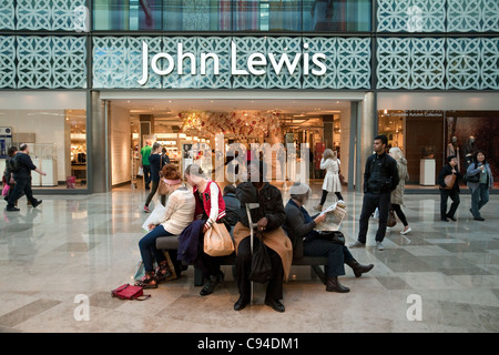 People sitting outside the John Lewis store, Westfield shopping centre Stratford London UK - Stock Photo