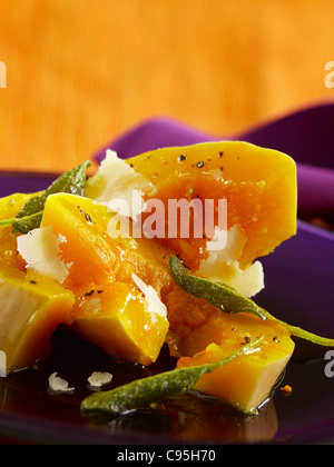 Butternut squash with sage leaves topped with shaved Parmesan - Stock Photo