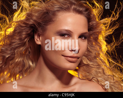 Beauty portrait of a young smiling woman with beautiful brightly lit flying golden hair - Stock Photo