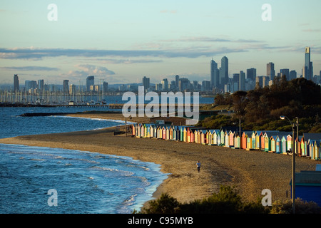 View of beach huts at Brighton Beach with city skyline in background.  Melbourne, Victoria, Australia - Stock Photo