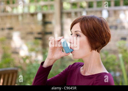 Asthma inhaler use. - Stock Photo