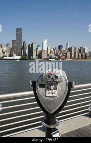 Coin operated binoculars overlooking East River towards Manhattan, New York - Stock Photo