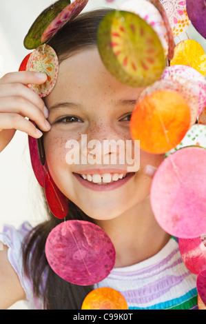 Germany, Bavaria, Girl looking through decorative sea shells wind chime - Stock Photo