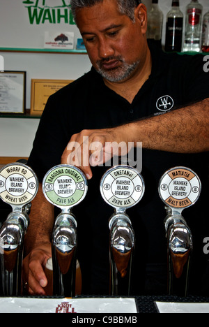 Publican pulling frosty pint of pale ale on tap from selection of beers at Wild on Waiheke brewery pub - Stock Photo