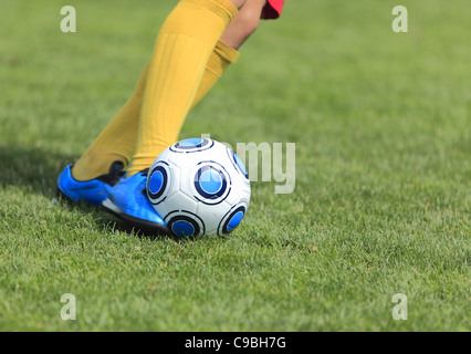 Detail image of a soccer player's leg when is kicking the ball - Stock Photo