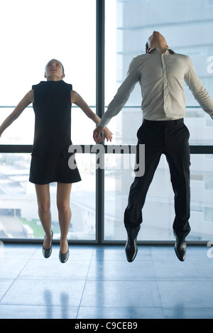 Businessman and businesswoman jumping - Stock Photo