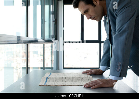 Businessman reading finance section of newspaper - Stock Photo