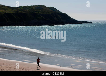Swansea - UK - 22nd May 2012 - A jogger and a pair of paddle boarders making the most of the sunshine at Langland - Stock Photo