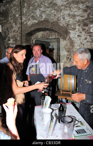 A Swiss wine producer pours a sample his wine for a visitor during a 'caves ouvertes' (open cellars) event. It is - Stock Photo