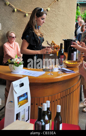 A Swiss wine producer pours a sample of her wine for a visitor during a 'caves ouvertes' (open cellars) event. It - Stock Photo