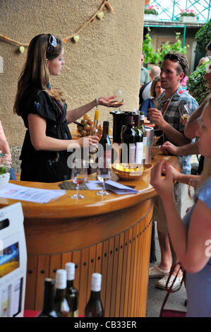 Mont sur Rolle, Switzerland, 27 May 2012. A Swiss wine producer pours a sample of her wine for a visitor during - Stock Photo
