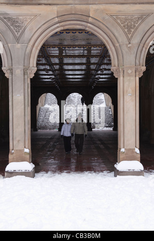 A couple walk through the Bethesda Terrace Arcade in Central Park in the New York winter - Stock Photo