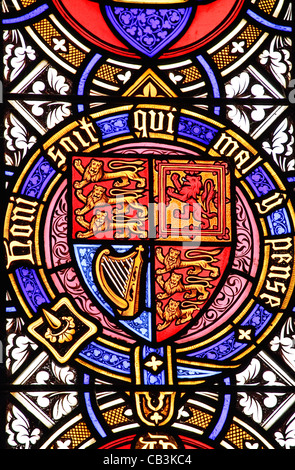 A stained glass window panel in a church depicting a Royal coat of arms and the motto 'Honi soit qui mal y pense' - Stock Photo