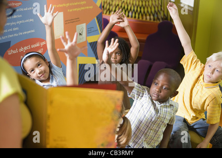 Students sitting in classroom, raising their hands to their teacher - Stock Photo
