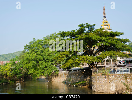 Mae Nam Sai river is border between Maesai Thailand & Tachileik Myanmar shown on right with river wall trees & tall - Stock Photo