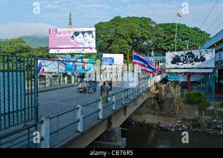 A tuk tuk and pedestrians cross international bridge between Thailand & Myanmar with sign 'Republic of the Union - Stock Photo