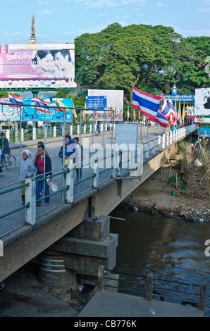 People walk and bicycle across international bridge over narrow river between Maesai Thailand and Tachileik Myanmar - Stock Photo
