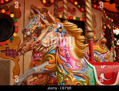 Brightly coloured carousel horses on a traditional merry go round ride in London, UK - Stock Photo
