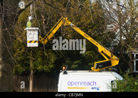 A BT ( openreach / open reach ) Engineer raised up in a hoist so he can fix a cable from a house to the telegraph - Stock Photo