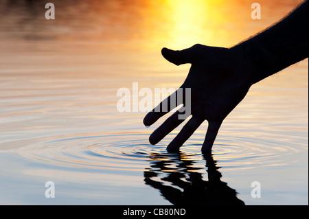 Hand touching water causing ripple at sunrise silhouette - Stock Photo