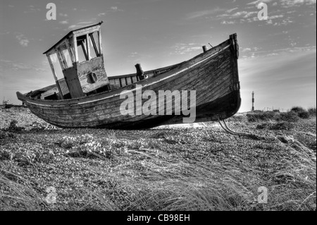 An old abandoned fishing boat on the beach at Dungeness, Kent, UK. The Dungeness lighthouse is in the background. - Stock Photo