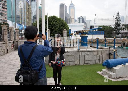 chinese female tourist poses for photograph at jardines noonday gun after the noon firing in hong kong hksar china - Stock Photo