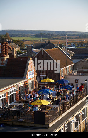 People enjoying a drink in the sunshine on the rooftop of Harbour Lights café bar restaurant in Yarmouth Isle of - Stock Photo