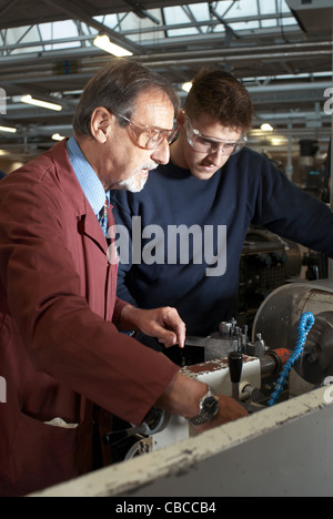 Teacher helping students in shop class - Stock Photo