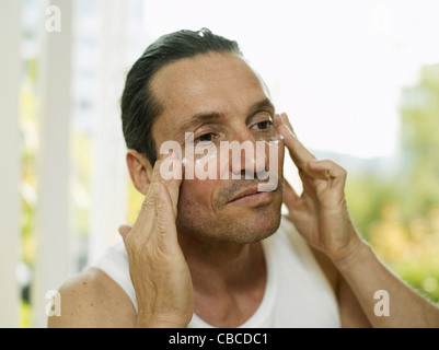Man applying moisturizer to face - Stock Photo