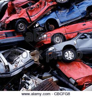 Wrecked cars in pile at junkyard - Stock Photo