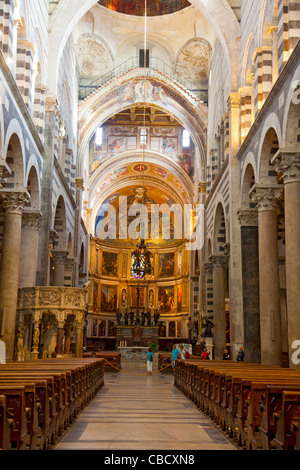 The interior of  11th century Pisa Duomo / Cathedral, looking down the nave towards the altar. Some tourists are - Stock Photo