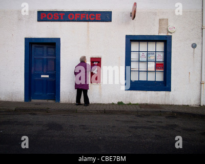 Woman Posting a Letter in Post Box, St Monans, Fife - Stock Photo