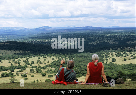 Olenkapune, Kenya. Middleaged white tourist couple resting on a hillside overlooking the Rift Valley in the Maasai - Stock Photo