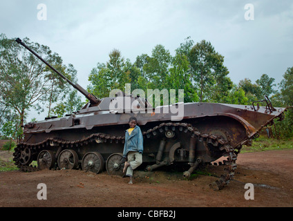 Boy In Front Of A Tank Wreck From Civil War, Bie Area, Angola - Stock Photo