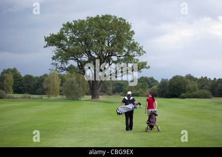 A female and male golfer walking with their golf bags, rear view - Stock Photo