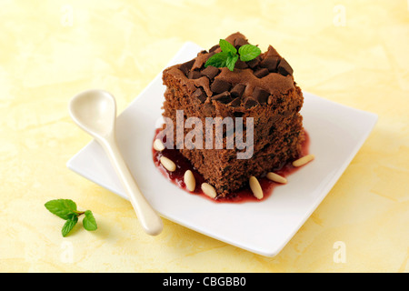 Brownie with cherry jam and pine nuts. Recipe available. - Stock Photo