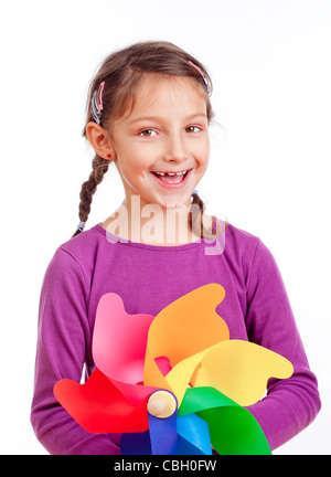 portrait of a little girl with braids holding a pinwheel - isolated on white - Stock Photo