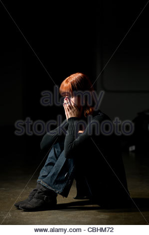 teen girl sitting on a floor in a darkened room looking depressed - Stock Photo