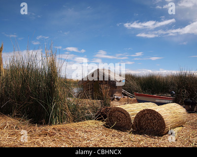 Hut made of reed and lots of drying reed on one of the floating Uros islands inside Lake Titicaca, Peru. - Stock Photo